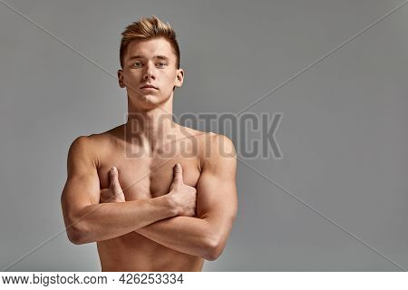 A Male Swimmer Stands With Crossed Arms, On A Gray Background, Challenging, Spears Space
