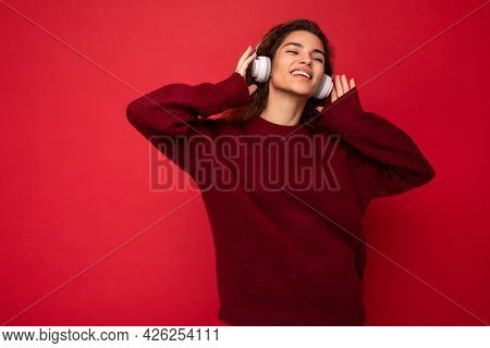 Photo Of Beautiful Happy Smiling Young Brunette Curly Woman Wearing Dark Red Sweater Isolated Over R
