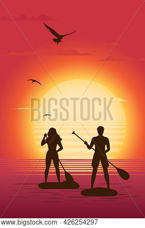 Silhouettes Of Man And Woman Standing On Paddle Board With A Paddle Against The Backdrop Of The Sett
