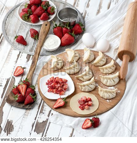 Sweet Dumplings Stuffed With Strawberries. Slices Of Raw Dough With Filling On Wooden Cutting Board.