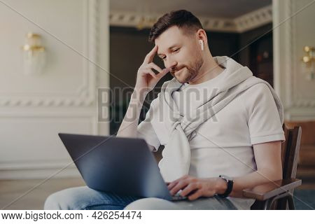 Handsome Bearded Man In Casual Clothes Concentrated At Laptop Computer Watches Webinar Communicates