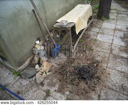 Pile Of Rubbish And Hand Tools In A Backyard, Outdoor Shot