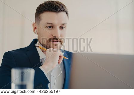 Professional Male Entrepreneur Focused At Laptop Uses Earphones Listens Necessary Information Watche