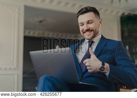 Successful Bearded Male Entrepreneur Dressed In Formal Suit Uses Modern Laptop Computer And Earbuds