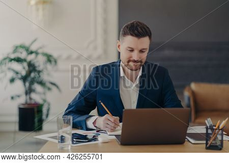 Indoor Shot Of Handsome Male Office Worker Rewrites Information From Notepad In Diary Sits At Desk D