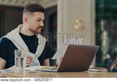 Smart Handsome Man Checks Information On Papers Works Remotely Sits At Home Office Uses Modern Lapto
