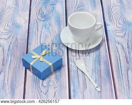 Porcelain Cup With Saucer, Spoon And Gift Box On Wooden Background.