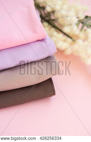 Colorful Cotton Folded Clothes Stack. Stack Of Multicolored Clothes On Pink Background. Set Of Cloth
