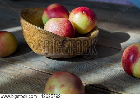 Red And Green Mini Nectarine In A Wooden Bowl. The Suns Rays Illuminate The Nectarine. Close-up.