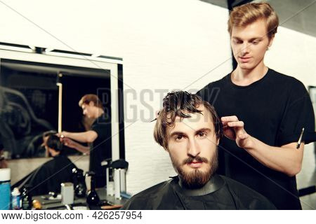 Barbershop. Good looking brunet man getting haircut by hairdresser while sitting in a chair at barbershop.