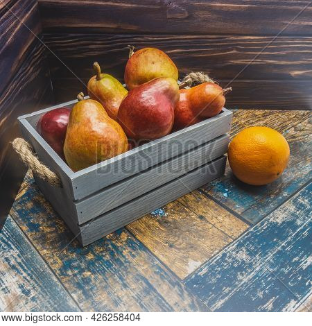 A Blue Wooden Box With Rope Handles Is Filled With Ripe Pears And Apples. Nearby, On The Boards, Lie