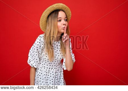 Photo Shot Of Young Beautiful Blonde Woman Wearing Casual Dress And Straw Hat Isolated Over Red Back