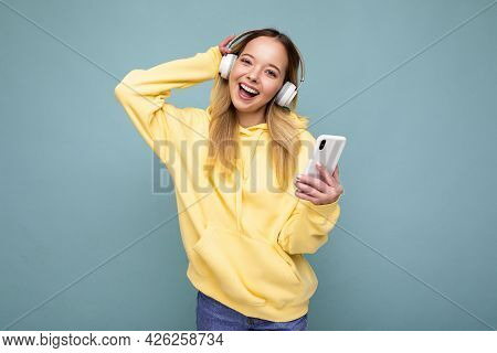 Beautiful Young Positive Blonde Woman Wearing Yellow Stylish Hoodie Isolated Over Blue Background We