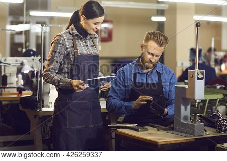 Two Shoe Factory Workers Checking The Quality Of New Footwear At Manufacturing Workshop