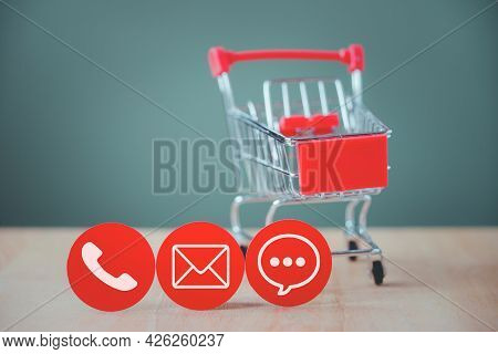 White Contact Symbol On Red Circle Paper Cut With Blurred Shopping Cart For Contact Us, Call, Mail O