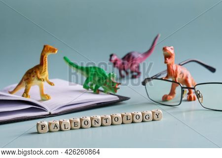 Paleontology Inscription Next To Toy Dinosaurs, Open Book Or Textbook And Glasses. The Concept Of St