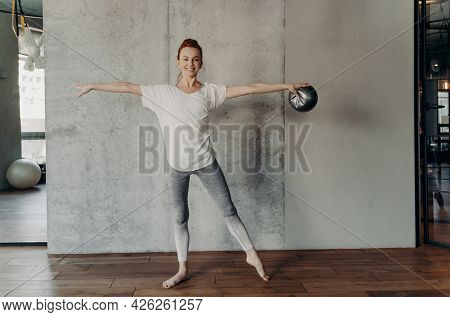 Beautiful Healthy Ginger Woman Performing Barre Exercises With Small Fitball, Standing In Second Pos