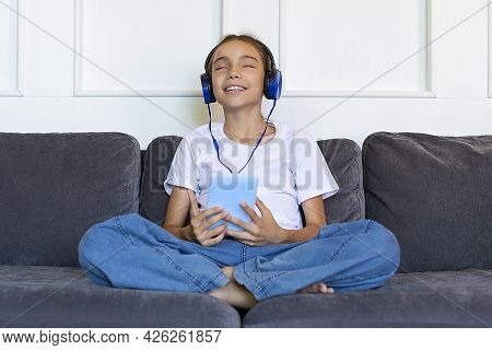 A Teenage Girl Sits On The Couch With A Tablet And Listens To Music Through Headphones.