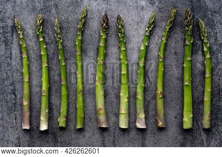 Green Fresh Raw Asparagus On Concrete Background. Bunch Of Fresh Asparagus Top View On Gray Concrete