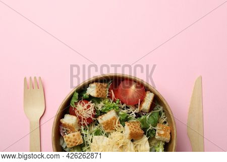 Bowl With Caesar Salad And Cutlery On Pink Background