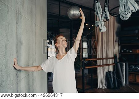Barre Workout. Smiling Female In Sportswear Standing Looking Up At Silver Pilates Small Exercise Bal
