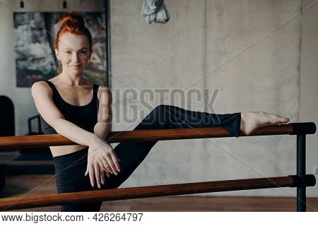 Beautiful Smiling Ginger Professional Female Dancer In Sportswear Stretching Warming Up Before Lesso