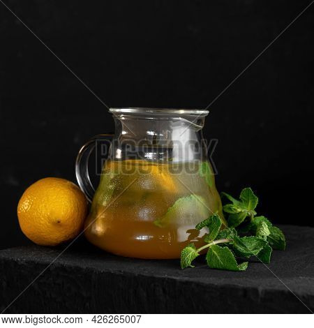Refreshing Mint And Citrus Lemonade. Cold Glass Jug With Yellow Drink, Lemon And Mint Sprig On Black