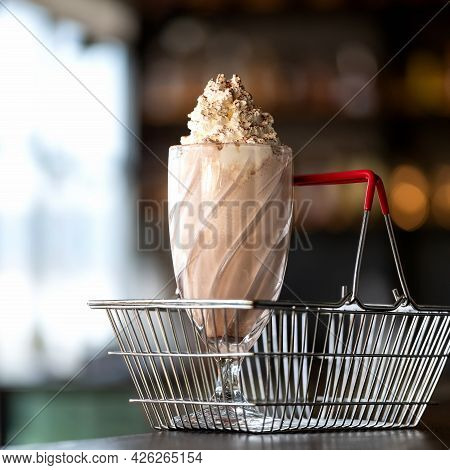 Refreshing Drink. Glass Of Milkshake Cocktail In Grocery Shopping Basket. Side View Of Cold Cream De