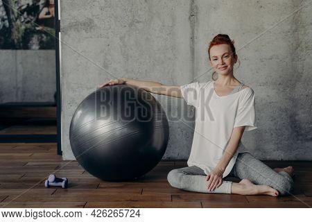 Young Smiling Red Haired Woman Posing With Large Exercise Pilates Fitball While Sitting On Floor Aga