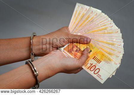 Woman Hands Hold Fan Of New Israeli Money Bills (banknotes) Of 100 Shekel In Handcuffs. Hands Office