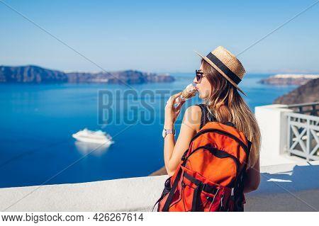 Woman Traveler Eating Ice-cream In Fira Santorini Island On Caldera Sea Background. Summer Vacation