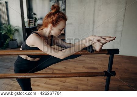 Young Redhaired Slim Female Ballerina Or Proffesional In Black Active Wear Dancer Exercising In Fitn
