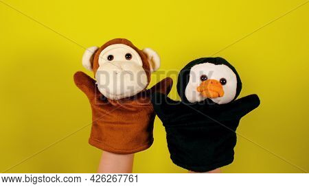Soft Puppet Toys On Hands On Yellow Background. Concept Of Puppet Show. Close-up Of Hands With Puppe