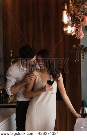 Man Seducing Smiling Woman In Slip Dress With Glass Of Wine