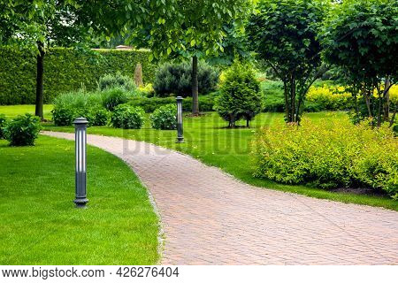 Curved Pedestrian Pavement Of Stone Tiles In Park With Landscaping And Green Plants Bushes With Tree