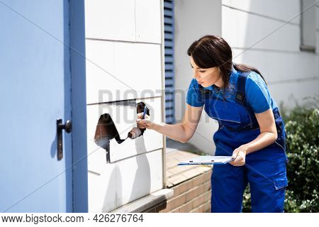 Real Estate Property Appraisal. Woman Inspecting House