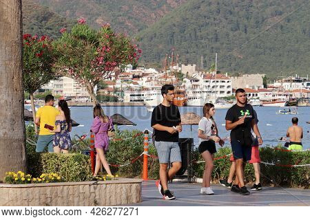 Marmaris, Turkey - July 2021: Tourists Walking On The Town Embankment. View Of The Harbour With Yach