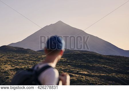 Traveler Against Landscape With Pico De Teide At Dusk. Young Man With Backpack Looking On Volcano. T