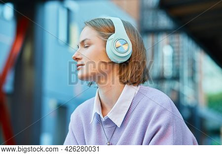 Melancholic Lady Student In Earphones Listens To Music