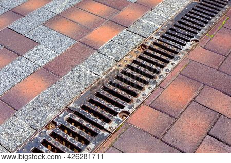 A Drainage Ditch Covered With An Iron Grate On A Sidewalk Made Of Stone Tiles And Granite Stones Clo