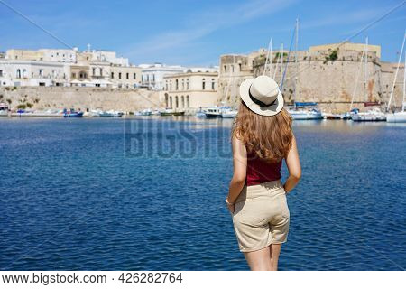 Beautiful Young Woman With Hat Looking At Historic Village Of Gallipoli In Salento, Italy