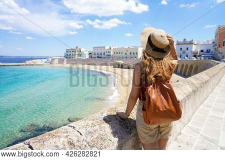 Summer Holiday In Italy. Back View Of Young Woman With Hat And Backpack In Gallipoli Village, Salent