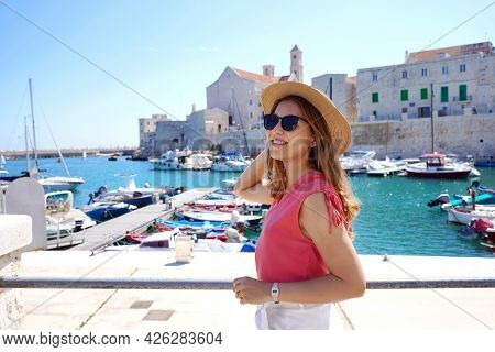 Beautiful Young Woman Wearing Sunglasses Walking Near The Old Harbor Of Giovinazzo, Apulia, Italy
