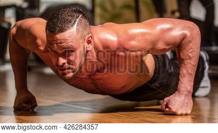 Muscular And Strong Guy Exercising. Slim Man Doing Some Push Ups A The Gym. Man Doing Push-ups. Musc