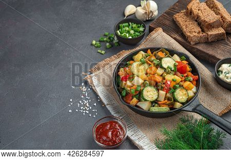 Baked Vegetables In A Serving Pan, Greens And Rye Bread On A Brown Background. Horizontal View, Spac