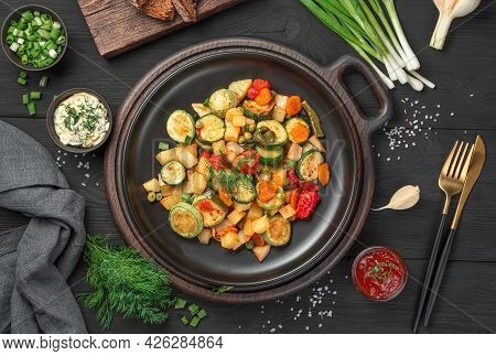 Fried Vegetables, Fresh Herbs And Sauces On A Black Background. Top View. Healthy, Organic Food.