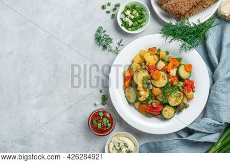 Healthy Stewed Vegetables In A White Plate On A Gray Background. Top View, Copy Space.