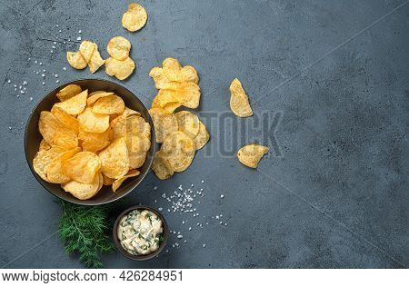 Potato Chips With Sour Cream And Dill On A Dark Gray Background. Top View, Copy Space.