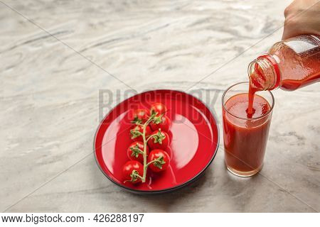 Pour Tomato Juice Into A Glass. Hand Pours Tomato Juice From Bottle Into Glass, Marble Table Top Bac