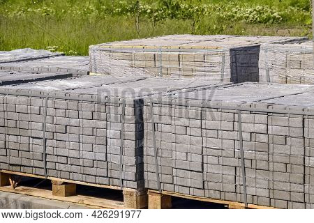 Pallets With Gray Paving Slabs On Background Of Green Grass. Plastic Packaging Protects The Tile Fro